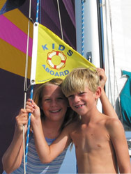 Alec and Emilie showing off their flag while cruising in the Caribbean with their family.